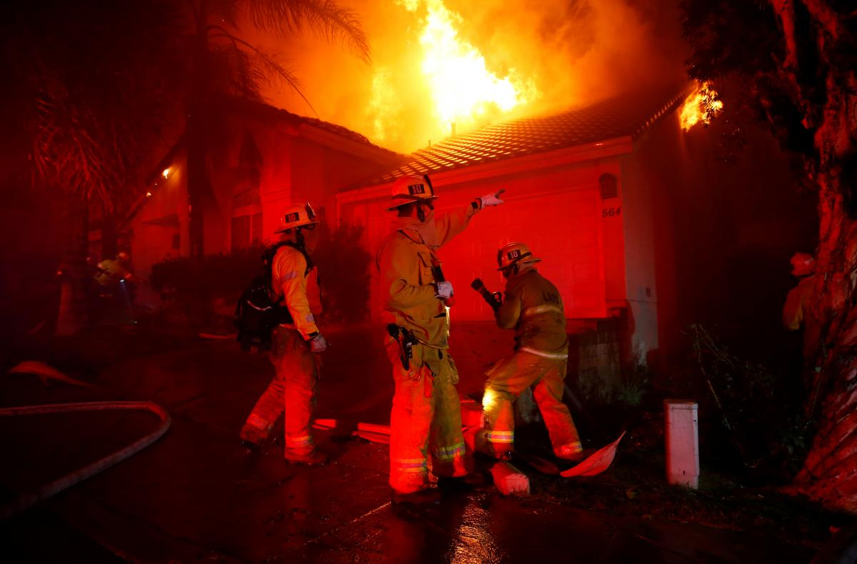 Firefighters try to beat back the Woolsey Fire in the early hours of Friday. One day earlier, the blaze ignited as mourning residents tried to cope with quite another kind of terror in Thousand Oaks, Calif.