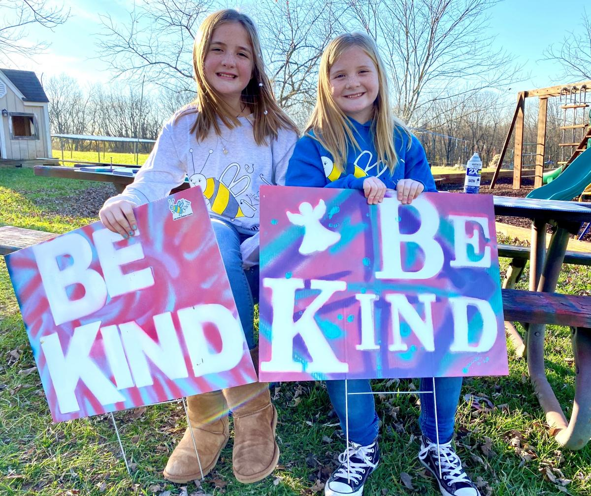On a November afternoon sisters Raegan and Rylyn Richins sit at their picnic table in their backyard in a Kentucky county holding signs they just painted.