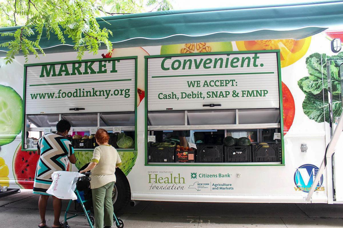 Customers check out the produce at a Curbside Market truck parked at Andrews Terrace, a large apartment complex in downtown Rochester. The program is part of Foodlink's efforts to help poor communities have access to fresh and healthy foods.