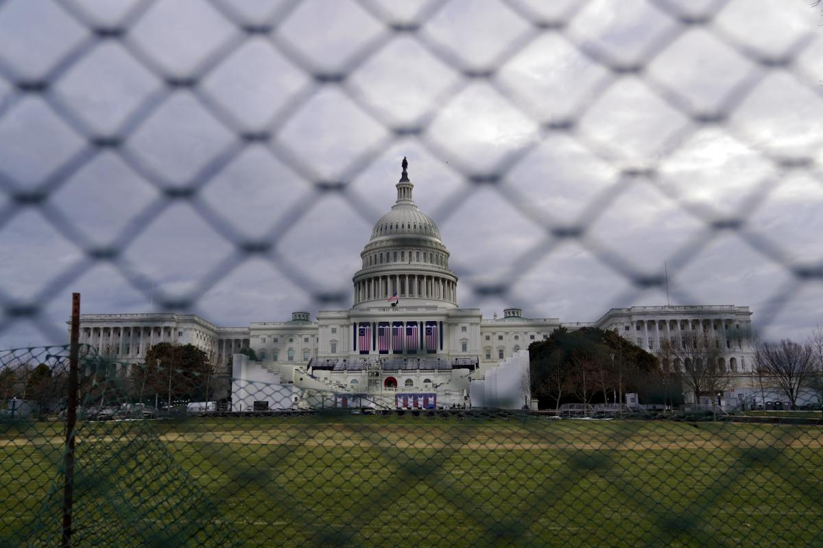 The U.S. Capitol is seen behind fences on Sunday, following the violent riot by pro-Trump extremists on Jan. 6. This week's events will have the largest security presence of any inauguration in U.S. history.