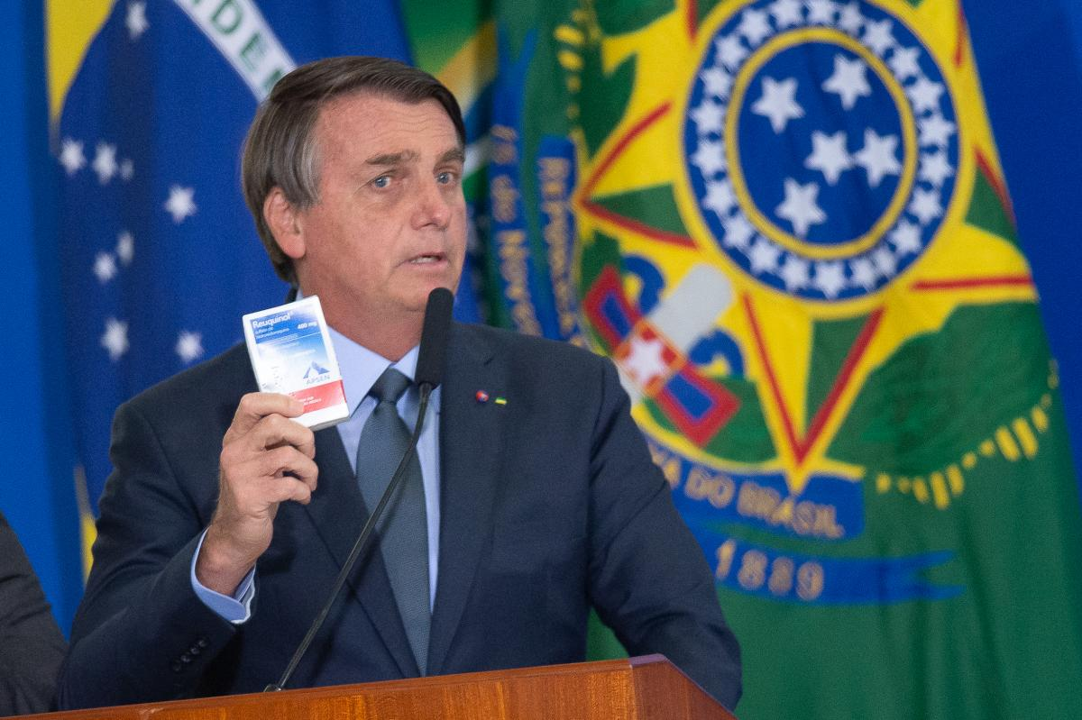 """Brazilian President Jair Bolsonaro holds up a box of chloroquine, an antimalarial medicine that his administration endorsed as part of an """"early treatment"""" strategy for COVID-19. There is no evidence the drug can prevent the coronavirus or reduce the seve"""