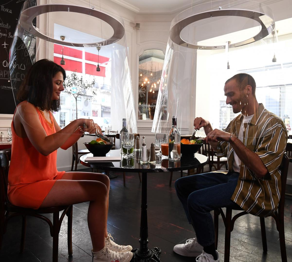 A couple has lunch under plexiglass protection designed by Christophe Gernigon at the H.A.N.D restaurant, on May 27, 2020, in Paris, as France eases lockdown measures taken to curb the spread of the COVID-19 pandemic.