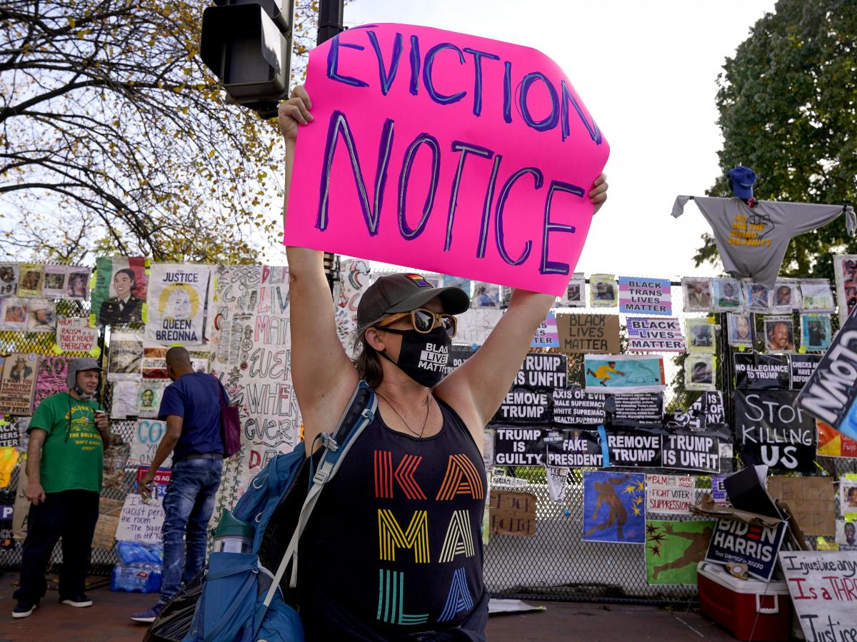 A protester holds up an eviction-related sign in Washington, D.C. The coronavirus rescue package just passed in Congress sets aside $25 billion for rental assistance and extends a CDC order aimed at preventing evictions.