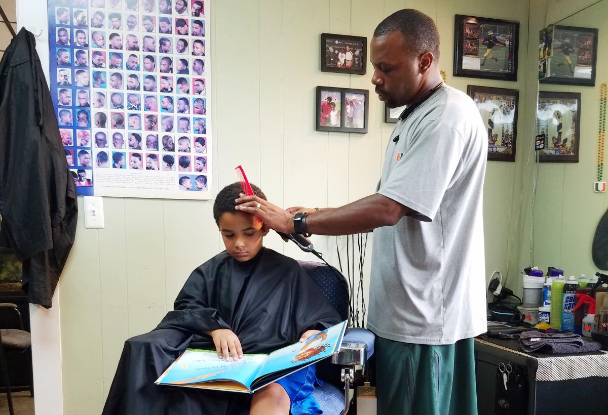 Jozef Jason, 7, reads a book to Ryan Griffin at the Fuller Cut in Ypsilanti, Mich., as part of the barbershop's literacy program.