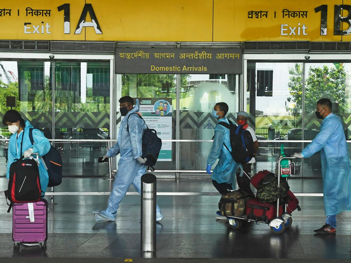 Air passengers wearing practically full-body coveralls at the Netaji Subhas Chandra Bose International Airport in India.