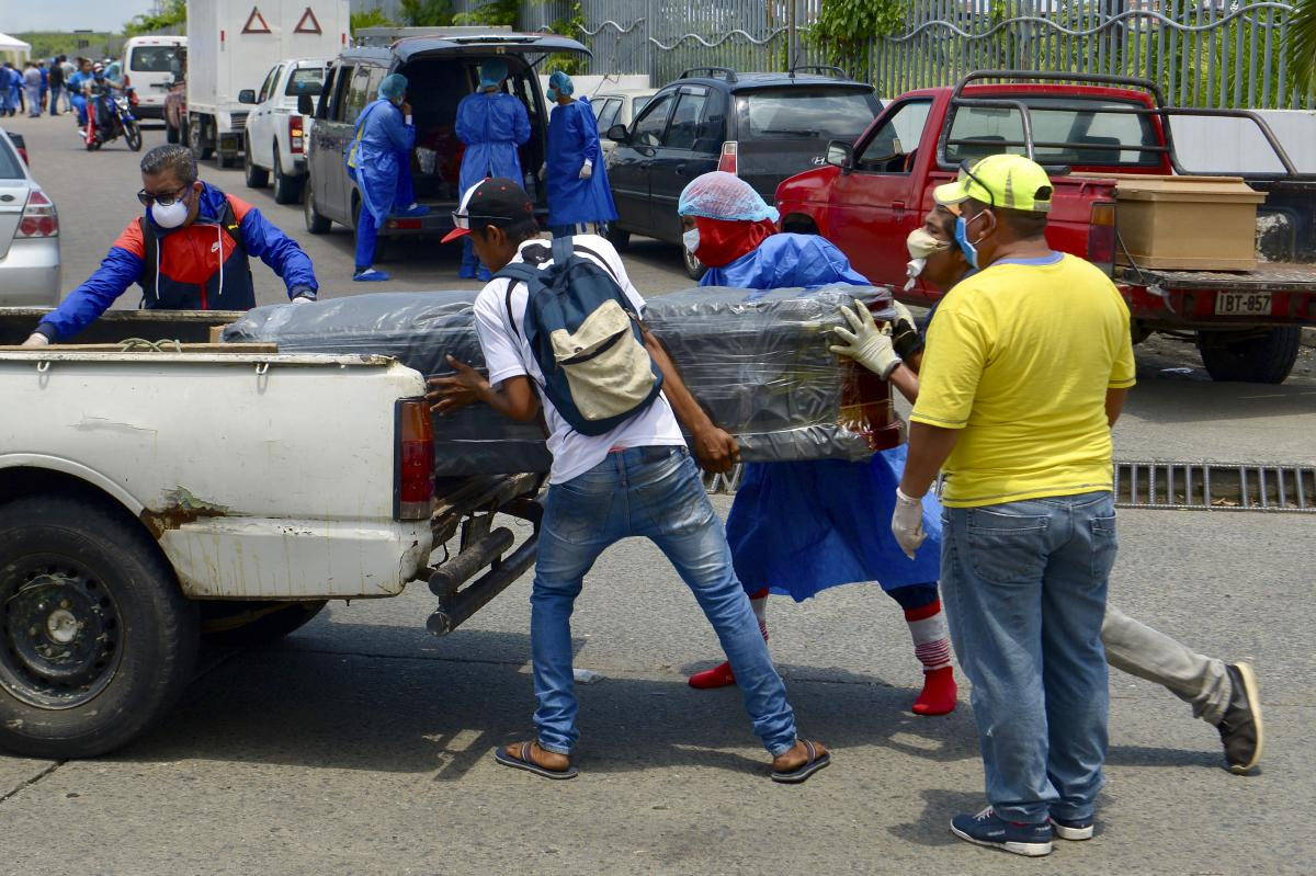Men load a coffin onto a pickup truck in front of General del Guasmo Sur Hospital in Guayaquil, Ecuador. The port city is the most affected by COVID-19 in the country. Corpses lie in apartments for days and morgues are overcrowded. The city administration