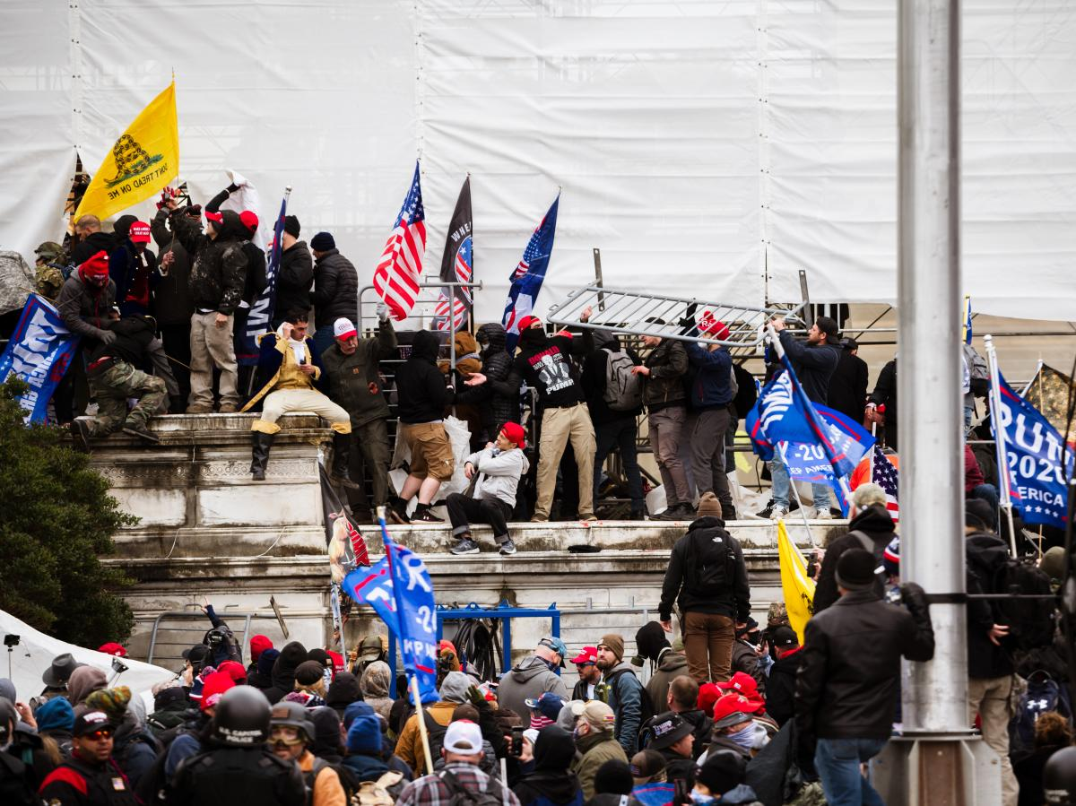 Pro-Trump extremists climb the walls of the U.S. Capitol on Jan. 6. The pro-Trump mob broke windows of the Capitol and clashed with police officers. Now there's debate about whether federal charges of seditious conspiracy should be used against some of th
