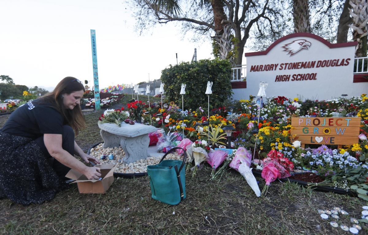 Suzanne Devine Clark, an art teacher at Deerfield Beach Elementary School, places painted stones at a memorial outside Marjory Stoneman Douglas High School during the one-year anniversary of the school shooting on Feb. 14, 2019, in Parkland, Fla. The stat
