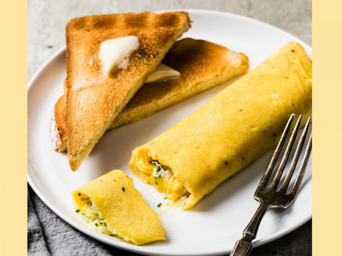 A French omelet, unlike its diner-style counterpart, is rolled, not folded, and include very little filling like vegetables and meats.