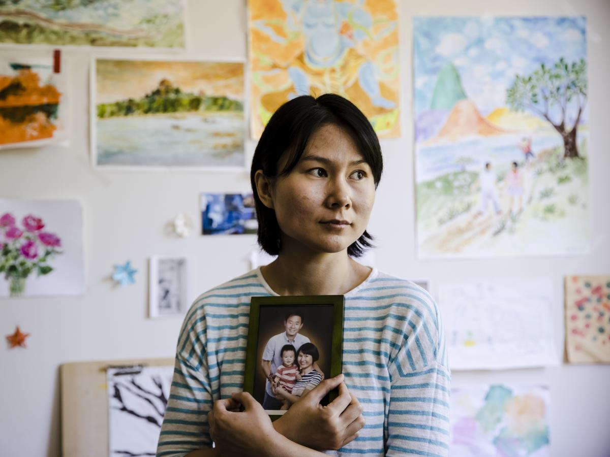 Hua Qu, the wife of Chinese-American Xiyue Wang, poses with a portrait of her family in Princeton, N.J., on May 9. Families of Americans detained in Iran are hoping President Trump's decision to withdraw from the Iran nuclear deal will not make it harder