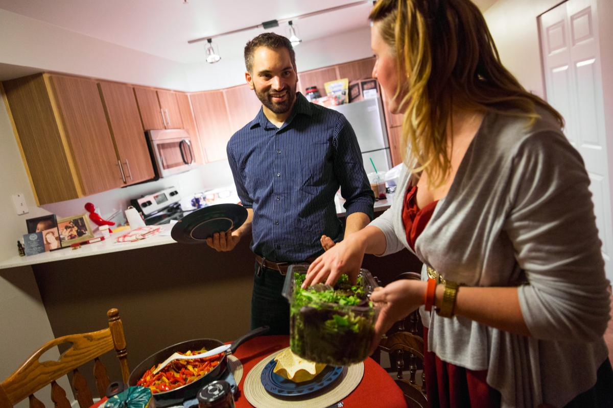 Carlos Romero and girlfriend Kate Rowe sit down for a meal they cooked together. Two years ago, Carlos Romero weighed 437 pounds.