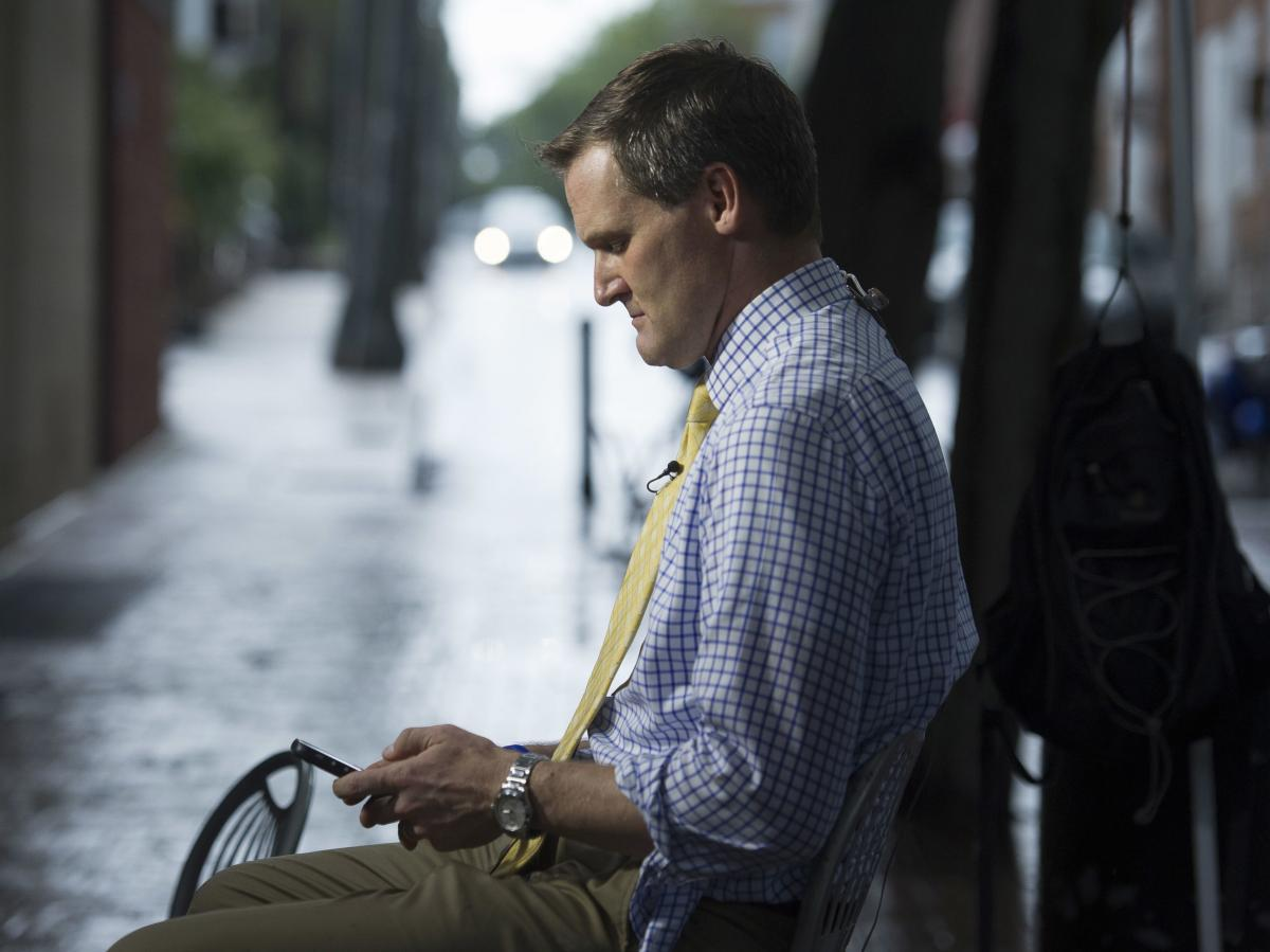 Charlottesville Mayor Mike Signer checks his phone while waiting to speak with a television network on Aug. 18, 2017. These days Signer travels the country presenting his city's experience as a cautionary tale.