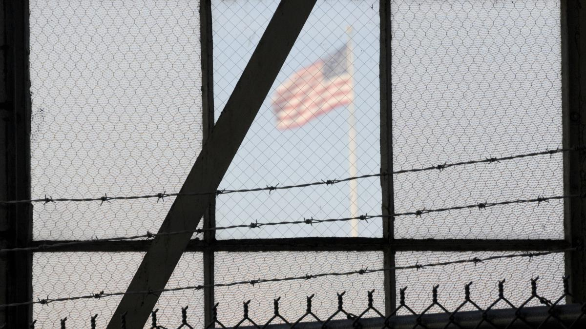 An NPR investigation finds that the military court and prison at Guantánamo Bay, Cuba, have cost taxpayers billions of dollars, with billions more expected. (Above) An American flag is seen through the war crimes courtroom at the U.S. naval base at Guant
