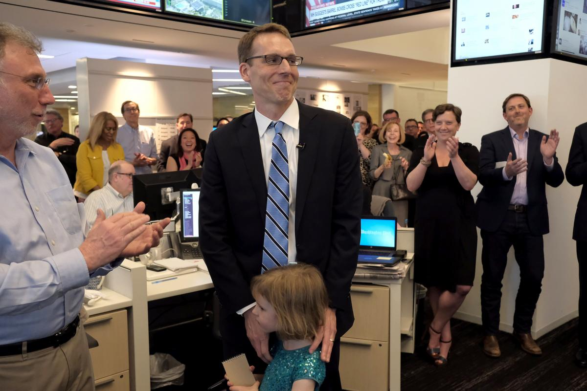 The Washington Post's David Fahrenthold (center) learns he won the 2017 Pulitzer Prize for national reporting, surrounded by his colleagues in the newsroom Monday.