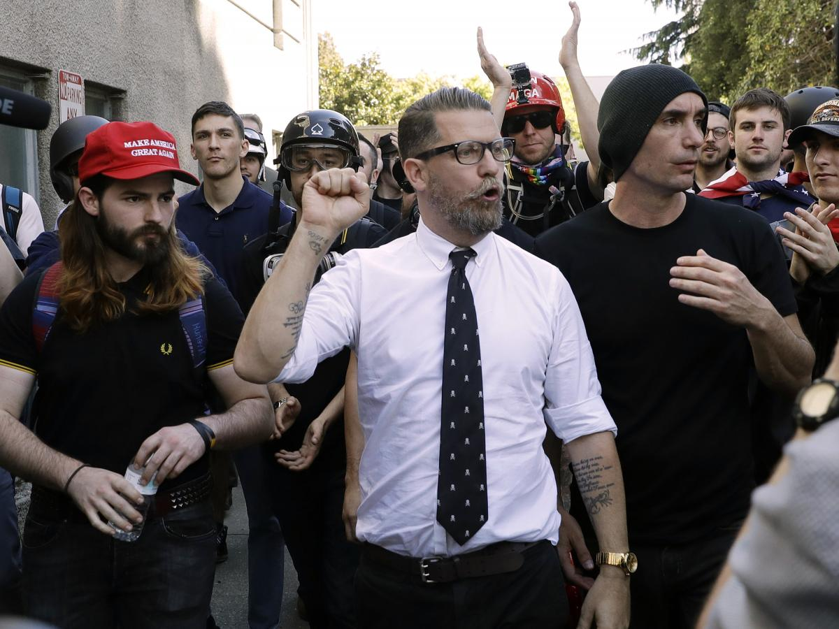 """In this 2017 photo, Gavin McInnes (center), founder of the far-right extremist group known as the Proud Boys, is surrounded by supporters after speaking at a rally in Berkeley, Calif. McInnes told NPR that the group is made up of """"funny dudes, not Nazis."""""""