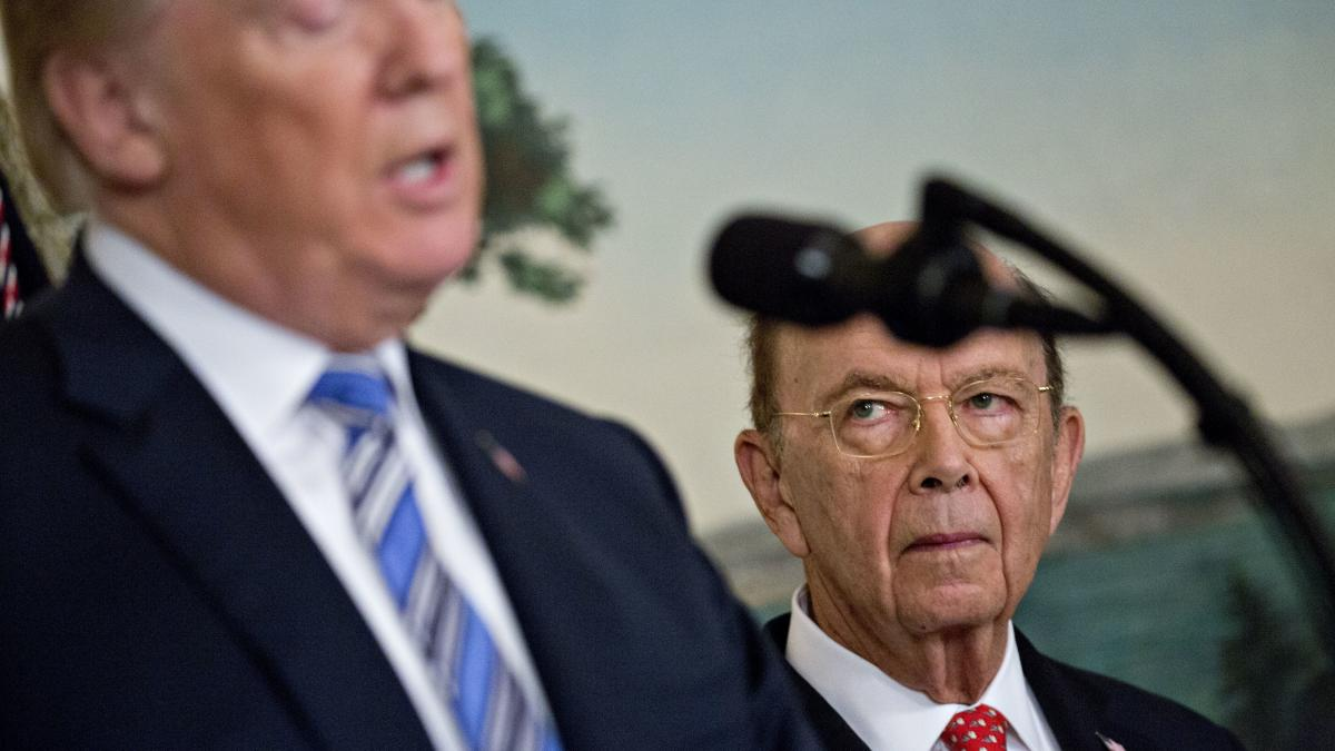 Commerce Secretary Wilbur Ross listens to President Trump at the White House in March. Ross' decision to add a question about U.S. citizenship status to the 2020 census sparked six lawsuits from dozens of states, cities and other groups that want the ques