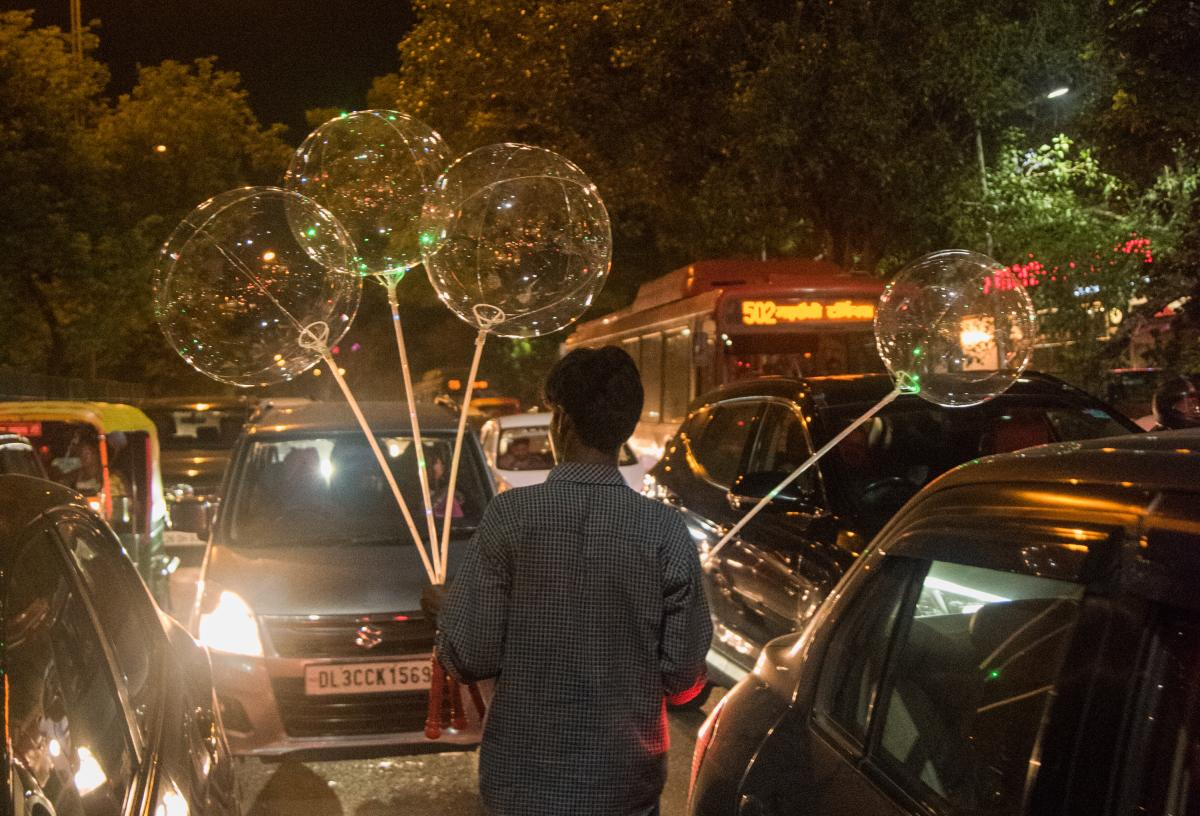 Radhesham Singh, a homeless 28-year-old street vendor in New Delhi, saunters amid traffic, selling balloons.