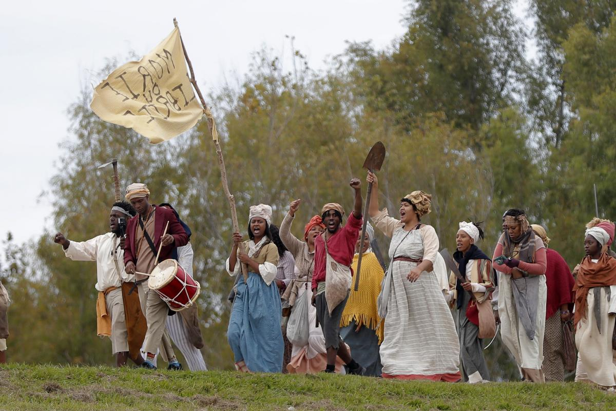 People march along the Mississippi River levee in Louisiana on Friday as they perform in a reenactment of the 1811 German Coast Uprising.