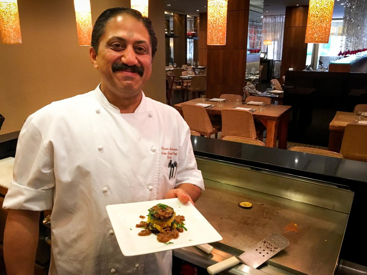 """Rasika chef Vikram Sunderam, here with a towering dish of eggplant and potato, says, """"Indian cuisine is a very personal cuisine. It's made from family to family, how they like to cook."""""""