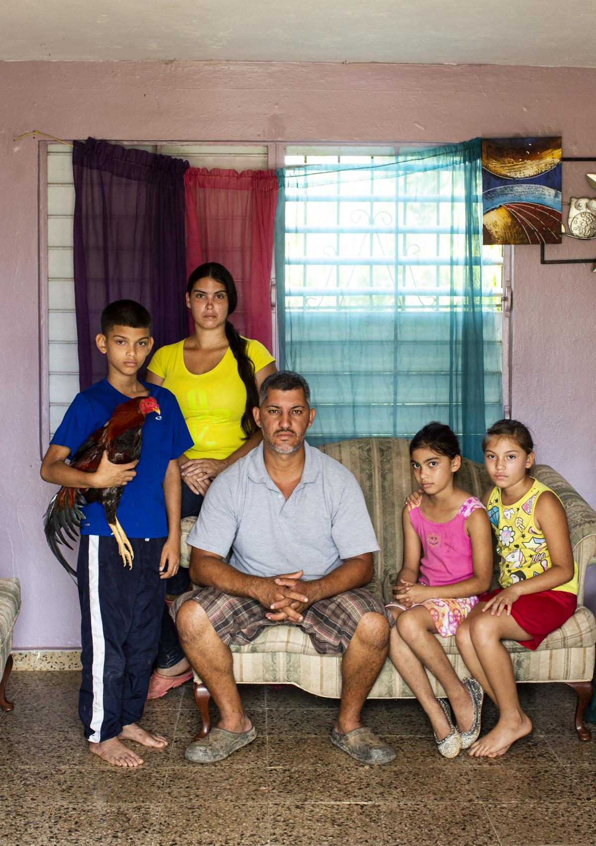 From left, José Yadiel Torres, 10, Lizmary Rivera, 29, José Torres, 38, and twins Janniela and Jamiléth Torres, 9, pose for a family portrait in their house in Utuado. The rooster, the family's most prized bird, is named Matatoro.