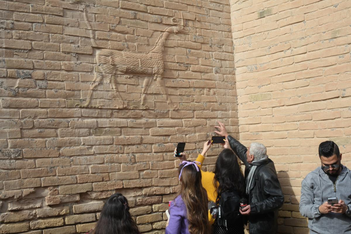 Visitors with the Bil Weekend tourism company take photographs inside the ruins of the ancient city of Babylon, in the area around the Ishtar gate. The animal on the walls ins a dragon-like creature associated with the Babylonian god Marduk.