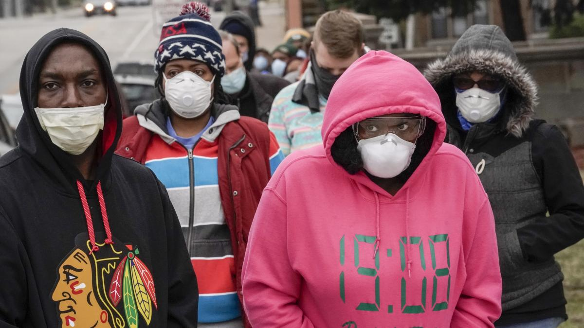 Voters masked to protect from the coronavirus line up at Riverside High School in Milwaukee. Voting went forward in the state, despite the ongoing pandemic.