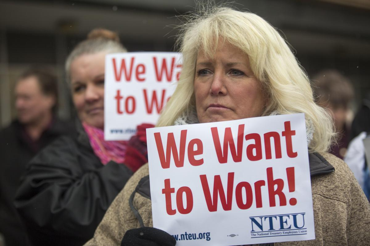 IRS employee Pam Crosbie and others hold signs protesting the government shutdown at a federal building in Ogden, Utah.