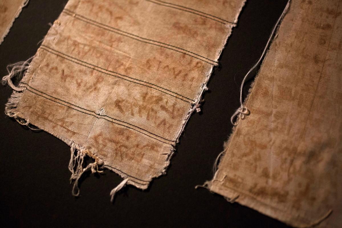 "Pieces of cloth that Mansour Omari and other inmates at a notorious Syrian prison used to document the names of the ""disappeared"" held with them. They made ink out of blood from their bleeding gums and rust from the prison bars."