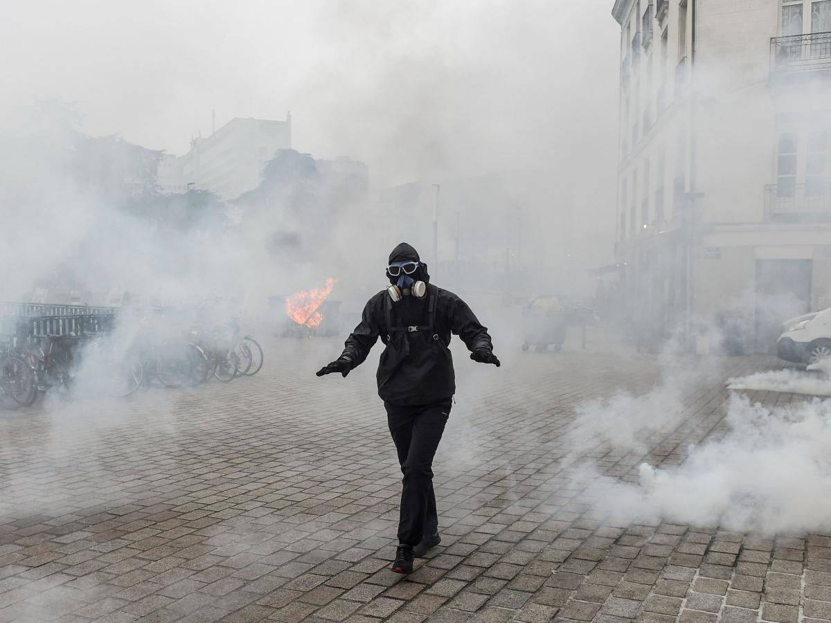 A protester walks through a cloud of tear gas during a demonstration against national pension changes in Nantes, France, on Thursday.