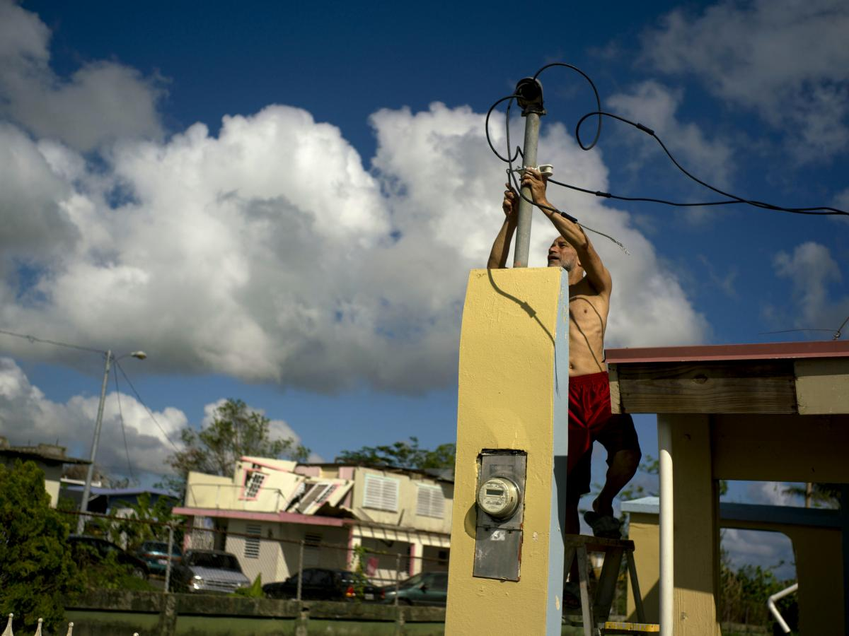 In October 2017, a resident tries to connect electrical lines downed by Hurricane Maria in Toa Baja. Puerto Rican officials say electricity has returned to all residents without it after the hurricane.
