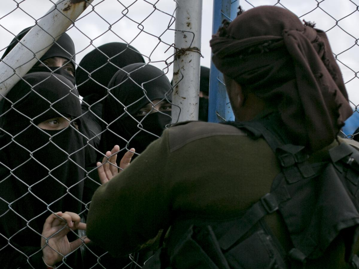 In this March 31, 2019, photo, women speak to guards at the gate that closes off the section for foreign families who lived in the Islamic State's so-called caliphate, at al-Hol camp in Hasakeh province, Syria.