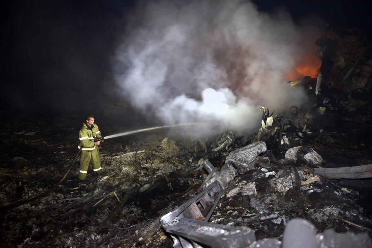 A firefighter douses the smoldering wreckage of Flight MH17 on Thursday.