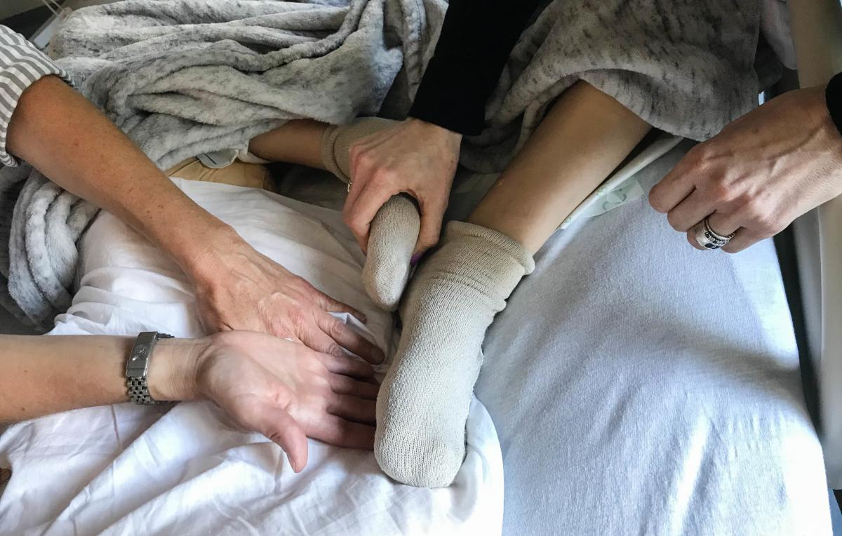Robyn Adcock (left), a University of California, San Francisco pain relief specialist, gently guides Jessica Greenfield to acupressure points on her son's foot and leg that have helped relieve his chronic pain.
