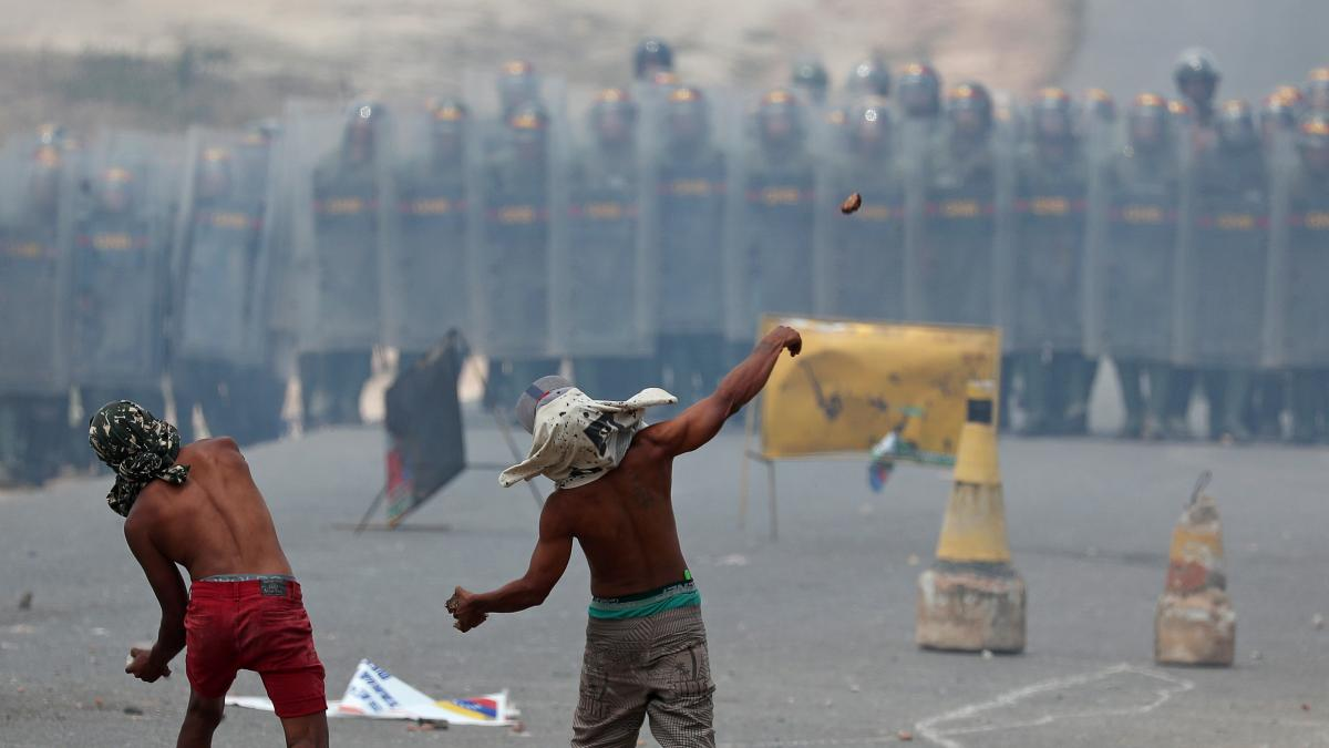 Demonstrators throw stones at a line of Venezuelan National Guard troops along Venezuela's border with Brazil, at the Brazilian city of Pacaraima on Sunday.