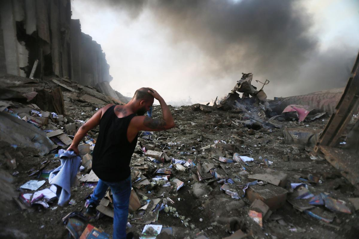 A man walks through debris near the scene of the enormous explosion in Lebanon on Tuesday. At least 70 people were killed, and at least 2,700 people were hurt. The blast shattered windows and damaged buildings across a wide swath of Beirut.