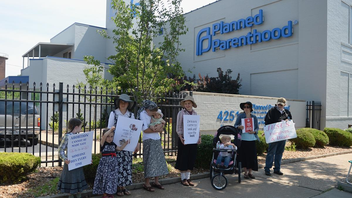 A group of anti-abortion rights protesters hold signs during a rally outside a Planned Parenthood Reproductive Health Center in St Louis, Mo., in June.