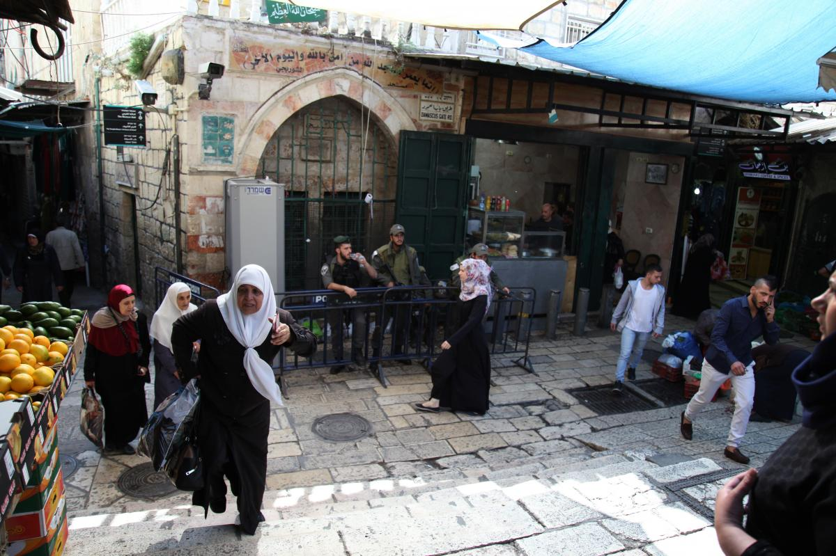 Palestinian shoppers walk near Damascus Gate in Jerusalem's Old City, under the watchful eye of Israeli police and wall-mounted security cameras. Amid the recent violence, there's talk of placing cameras inside the city's most contested religious site, kn