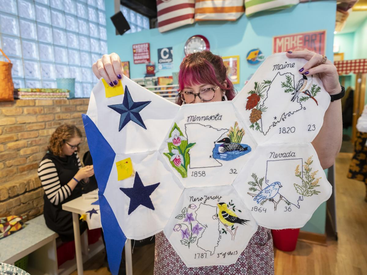 Jenni Grover holds a collection of finished patches from a quilt created by more than 100 volunteers across the country. The plans for the quilt were discovered at the estate sale of 99-year-old Rita Smith, who died earlier this year. Several dozen volunt