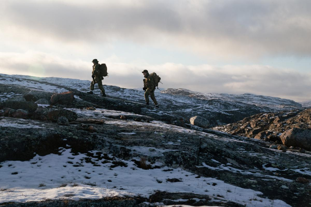 Two privates walk on the mountain just outside the border post.
