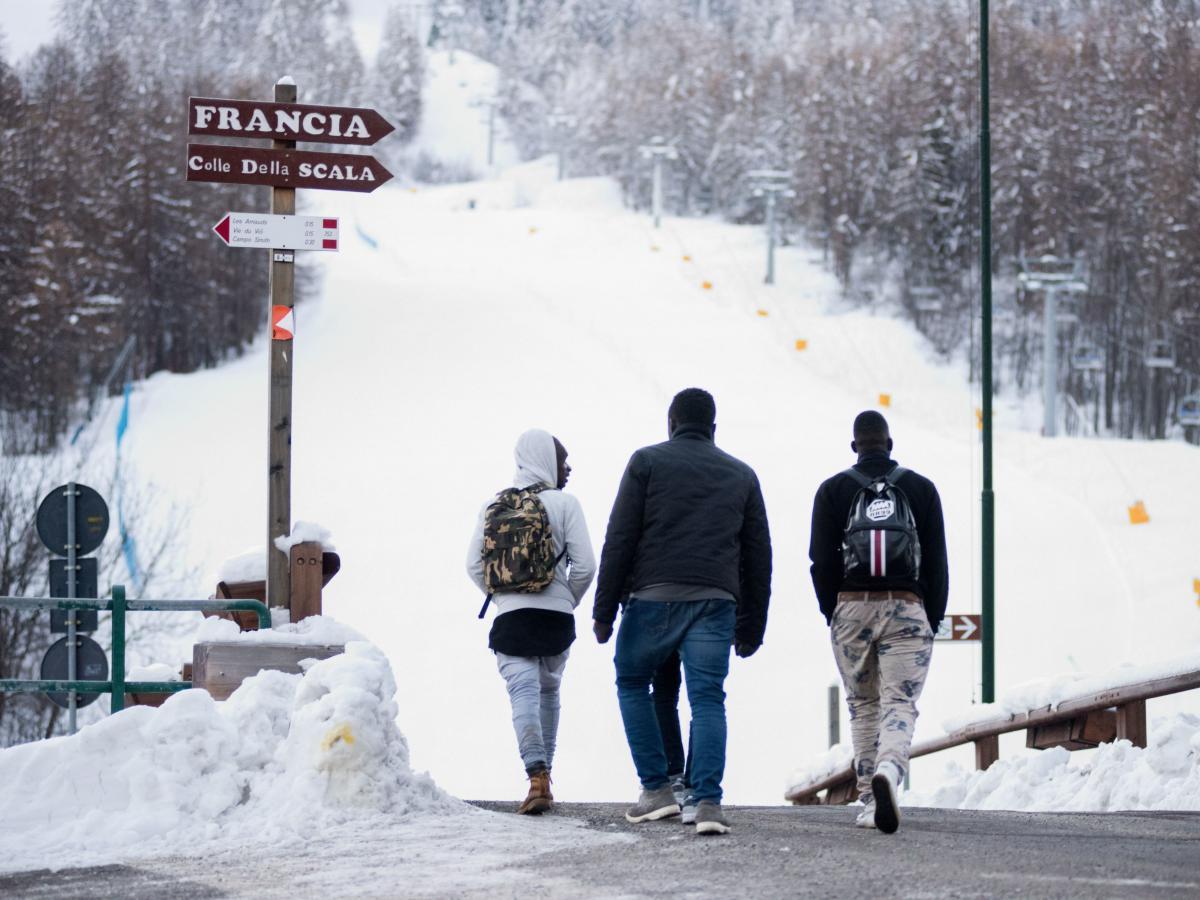 Migrants walk toward a snow-covered pass to cross the border from Italy to France, in January 2018 near Bardonecchia, Italian Alps.