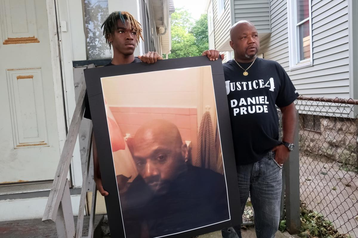 """Family members Armin Prude (left) and Joe Prude stand with a picture of Daniel Prude in Rochester, N.Y., Thursday, Sept. 3, 2020. While suffering a mental health crisis, Prude, 41, suffocated after police in Rochester put a """"spit hood"""" over his head while"""