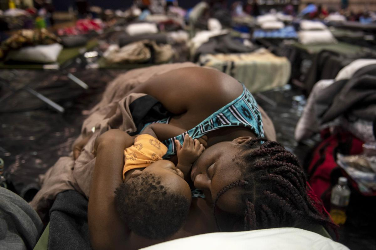 A woman holding a child sleeps after being evacuated at Southeast Raleigh High School ahead of Hurricane Florence in Raleigh N.C. on Wednesday