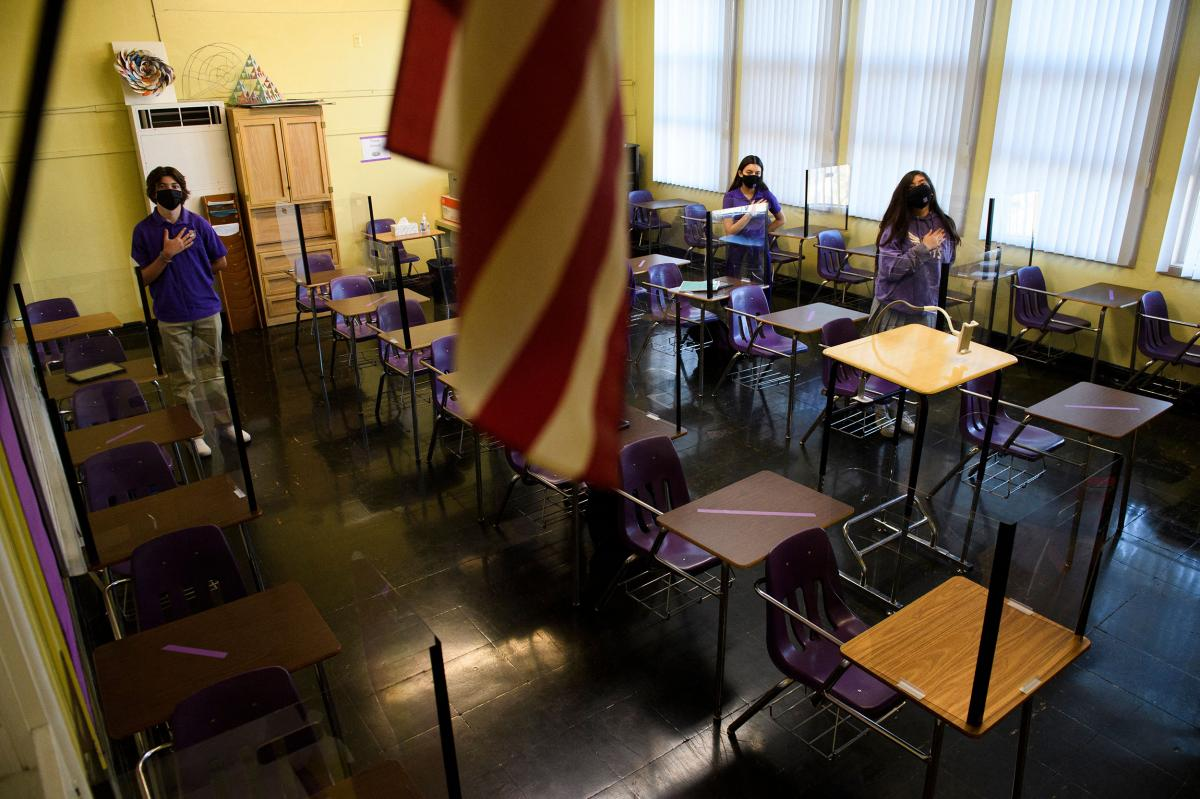 Students stand for the Pledge of Allegiance as they return to in-person learning at St. Anthony Catholic High School in California on March 24. Masks and physical distancing are proving to have some major public health benefits, keeping people from gettin