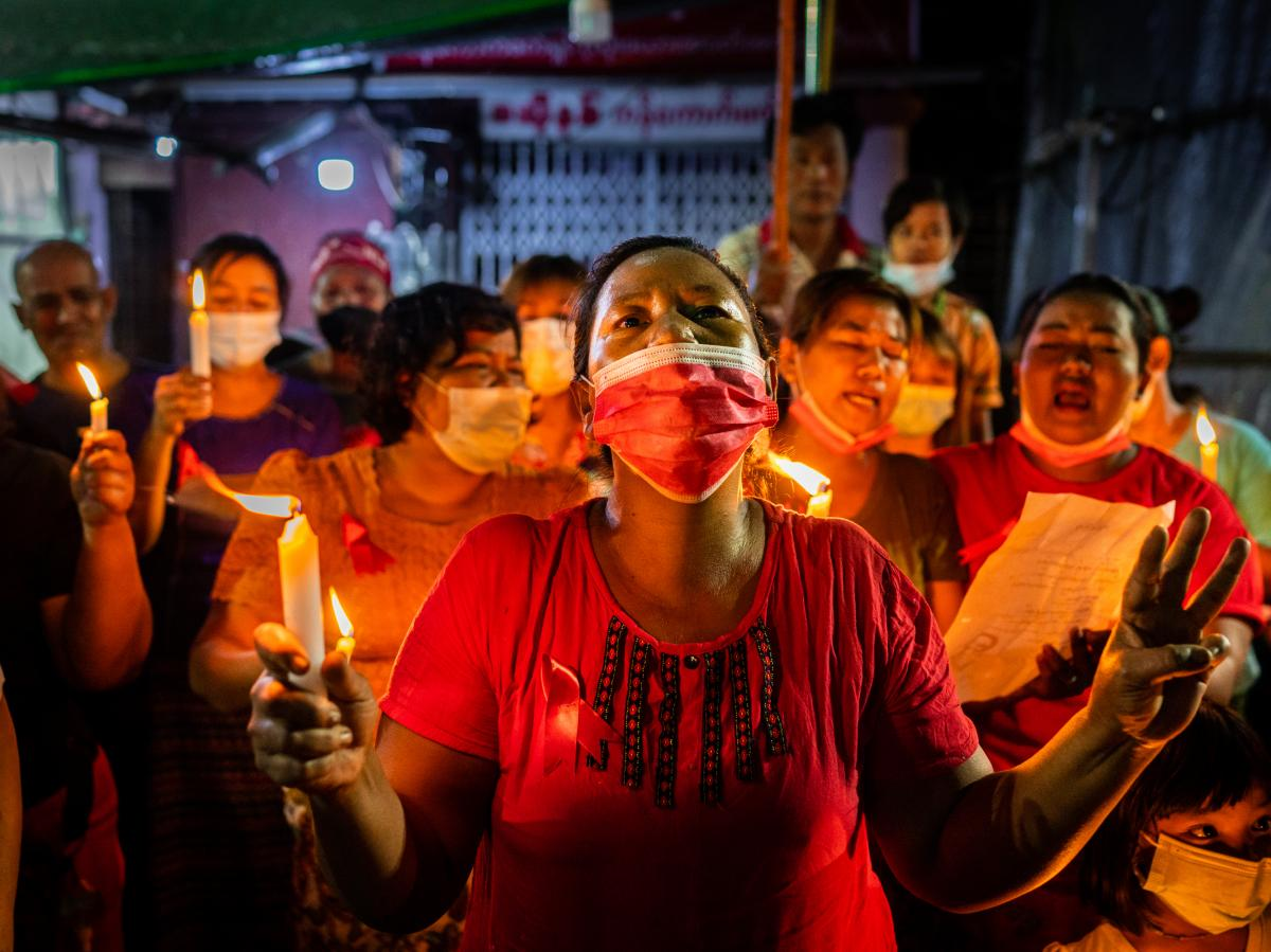 People hold candles and make a three-finger salute in a market on Feb. 5 in Yangon, Myanmar. People in Myanmar continue to take part in acts of civil disobedience in protest against the Feb. 1 military coup.
