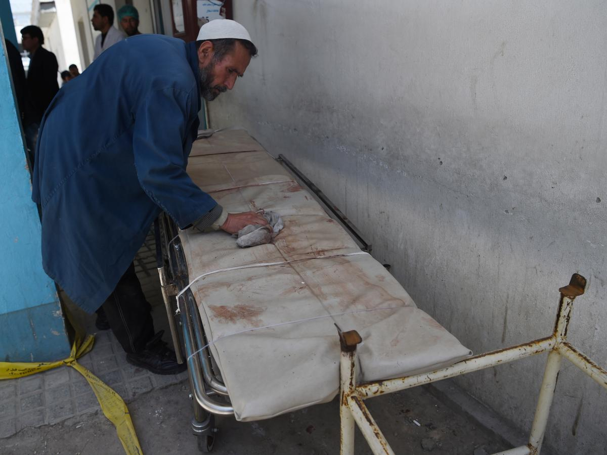 An Afghan member of medical staff cleans a stretcher following a suicide bombing attack in Kabul on April 22, 2018. (Photo by WAKIL KOHSAR / AFP) (Photo credit should read WAKIL KOHSAR/AFP/Getty Images)