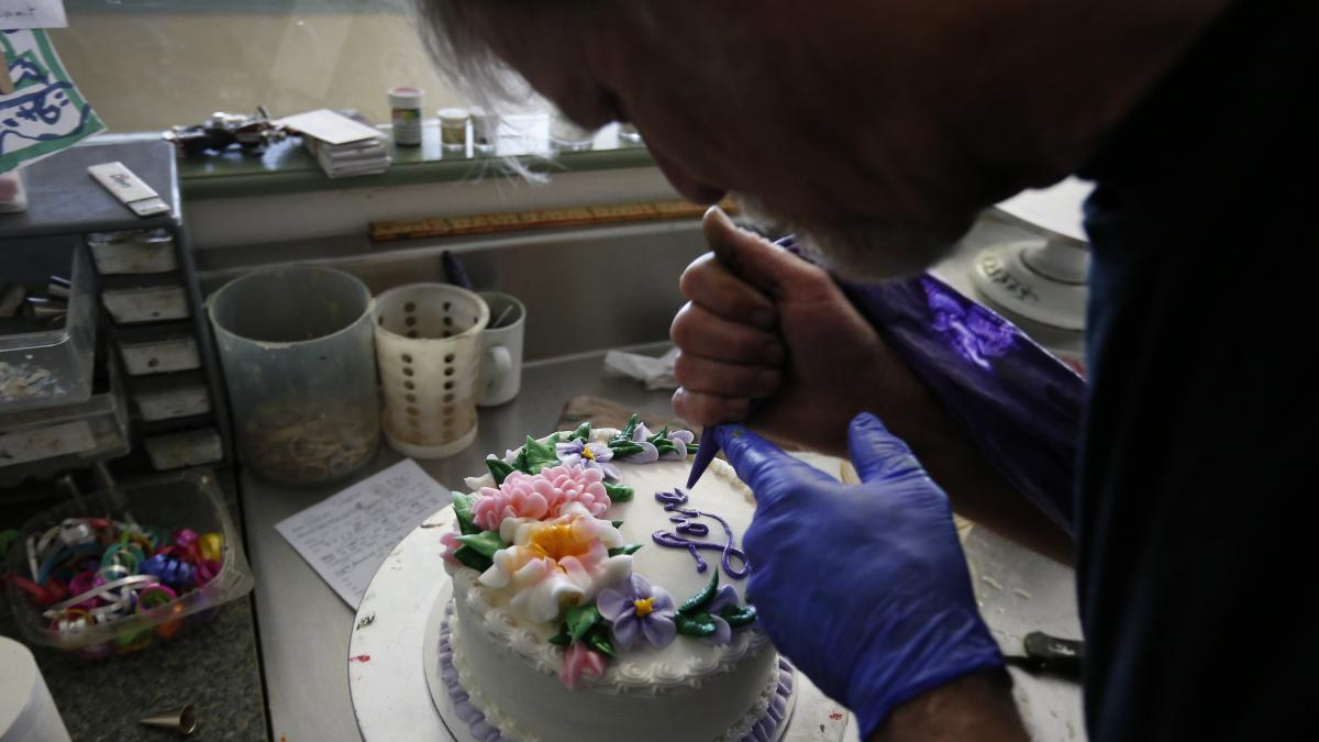 In this March 10, 2014, photo, Masterpiece Cakeshop owner Jack Phillips decorates a cake inside his store, in Lakewood, Colo.