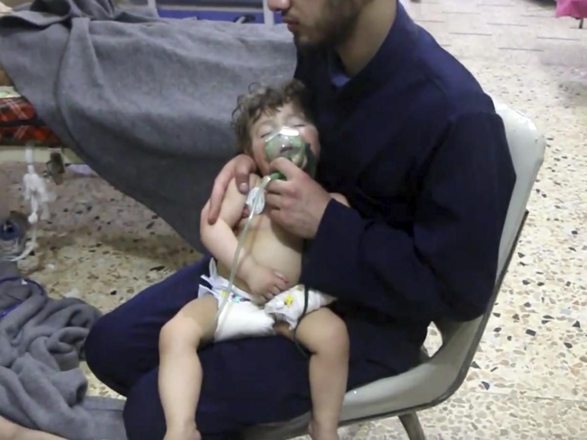 This image made from video shows a medical worker administering oxygen through respirators following an alleged poison gas attack in Douma. The Syrian government denied the allegations.