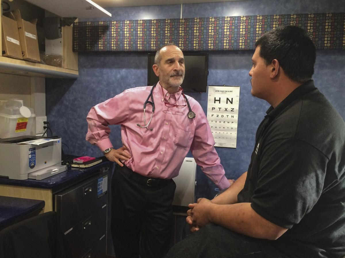 Inside a mobile clinic parked near a Conservation Corp high school, Dr. Seth Ammerman talks with a patient. About 400 young people who visit the van each year have never seen a doctor, Ammerman says.
