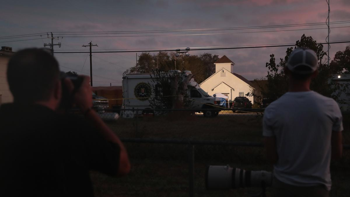 Newspaper photographers look on as the sun rises over the First Baptist Church in Sutherland Springs, Texas, the site of a mass shooting during a Sunday service.