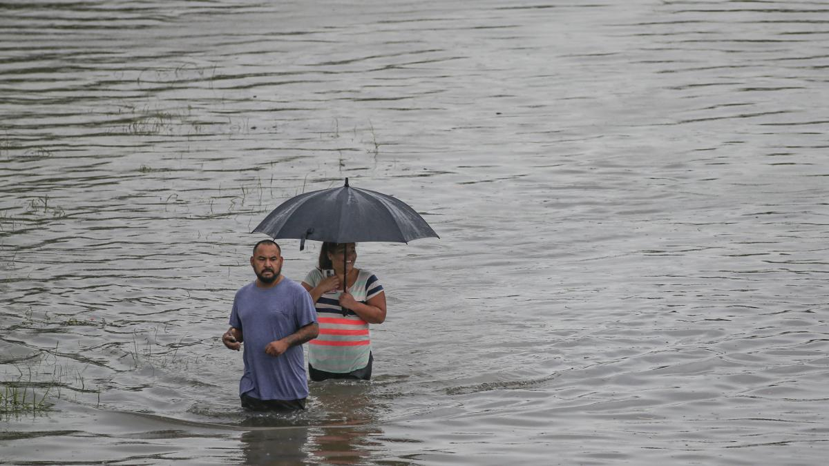 People in Houston navigate the floodwaters on Thursday. The city got more than 9 inches of rain on that day alone, according to the National Weather Service in Houston.